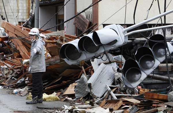 "<div class=""meta image-caption""><div class=""origin-logo origin-image ""><span></span></div><span class=""caption-text"">A construction laborer controls the traffic at a devastated area in Kesennuma, Miyagi Prefecture, northern Japan, Wednesday, March 16, 2011, after Friday's powerful earthquake-triggered tsunami hit Japan's east coast.  ((AP Photo/Shizuo Kambayashi) )</span></div>"